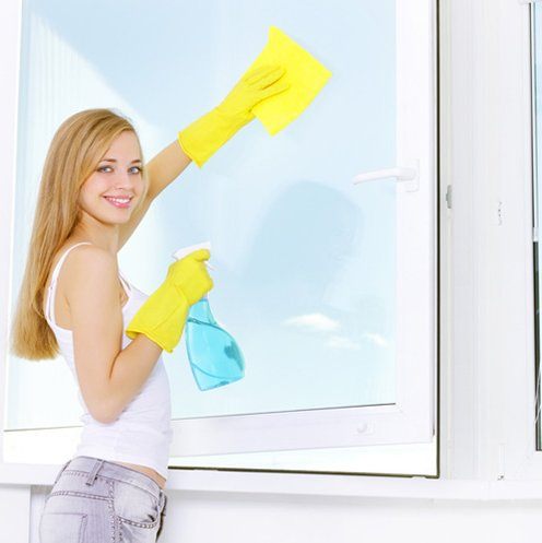 Smiling girl washing windows